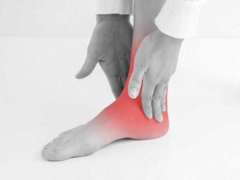 怪我をして足を押さえる人