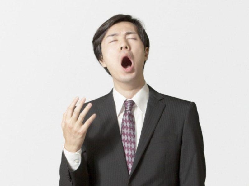 あくびをするスーツを着た男性