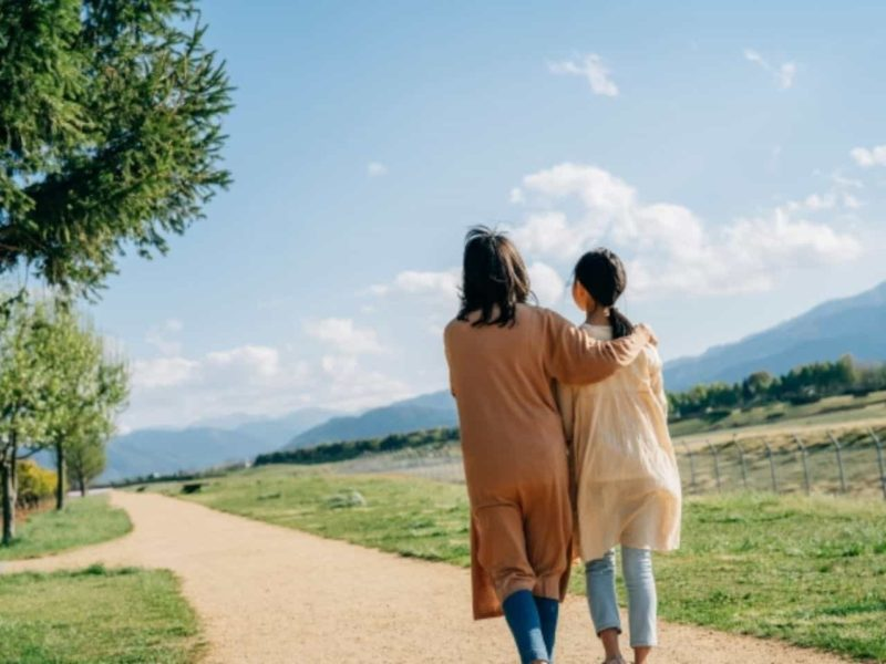 公園を歩く母親と娘