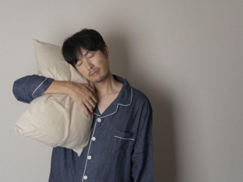 枕を抱いて眠っている男性