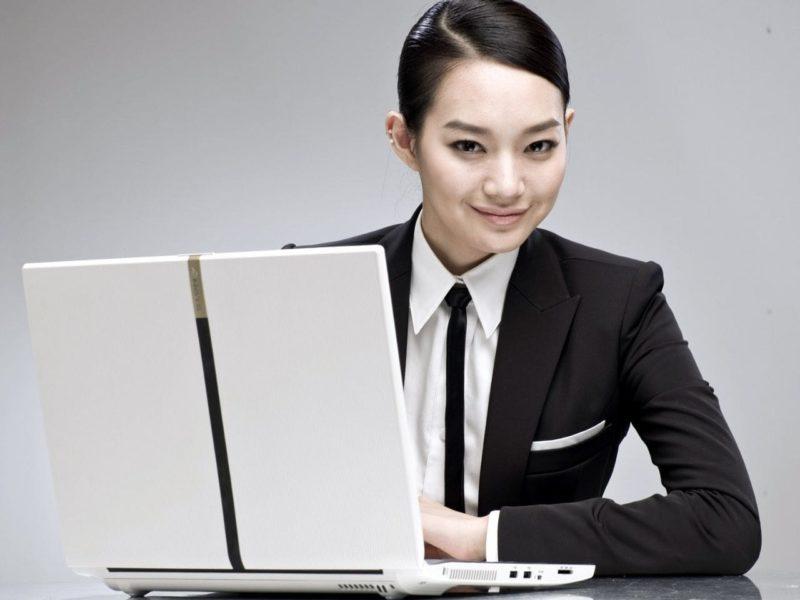 ノートパソコンの前で微笑む女性